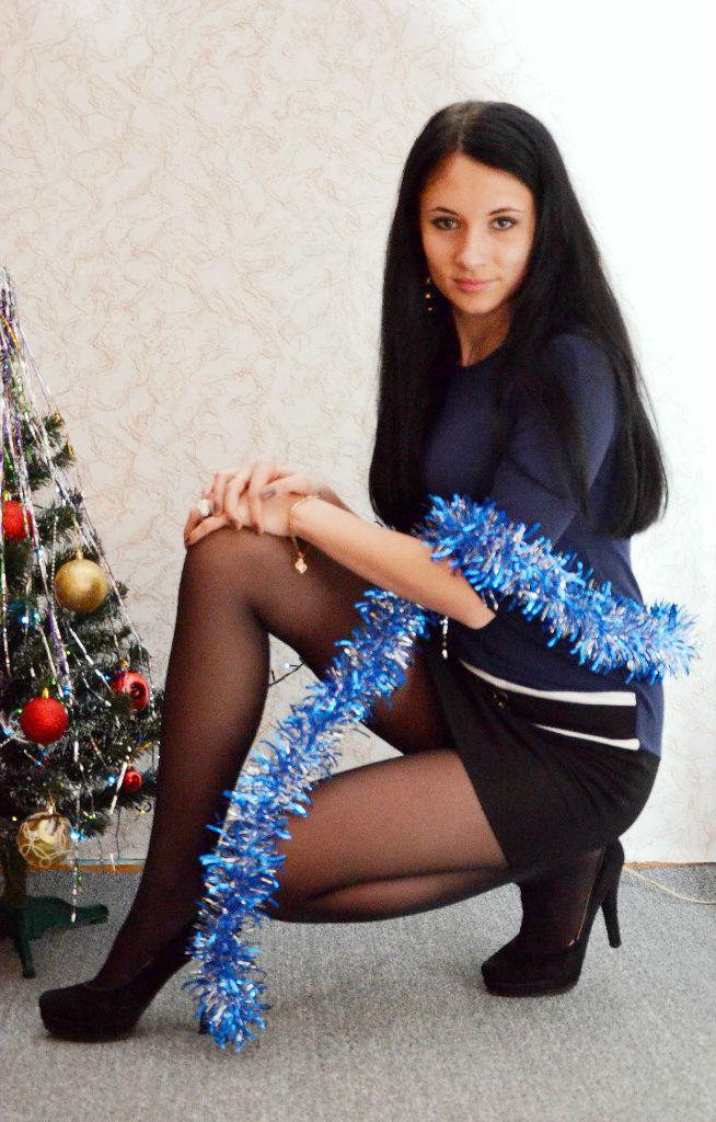 Девушка в колготках возле новогодней елки