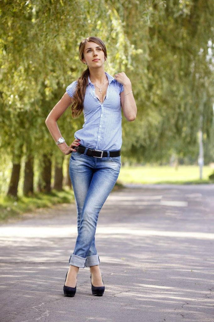 Девчонка прогуливается под ивами в джинсах