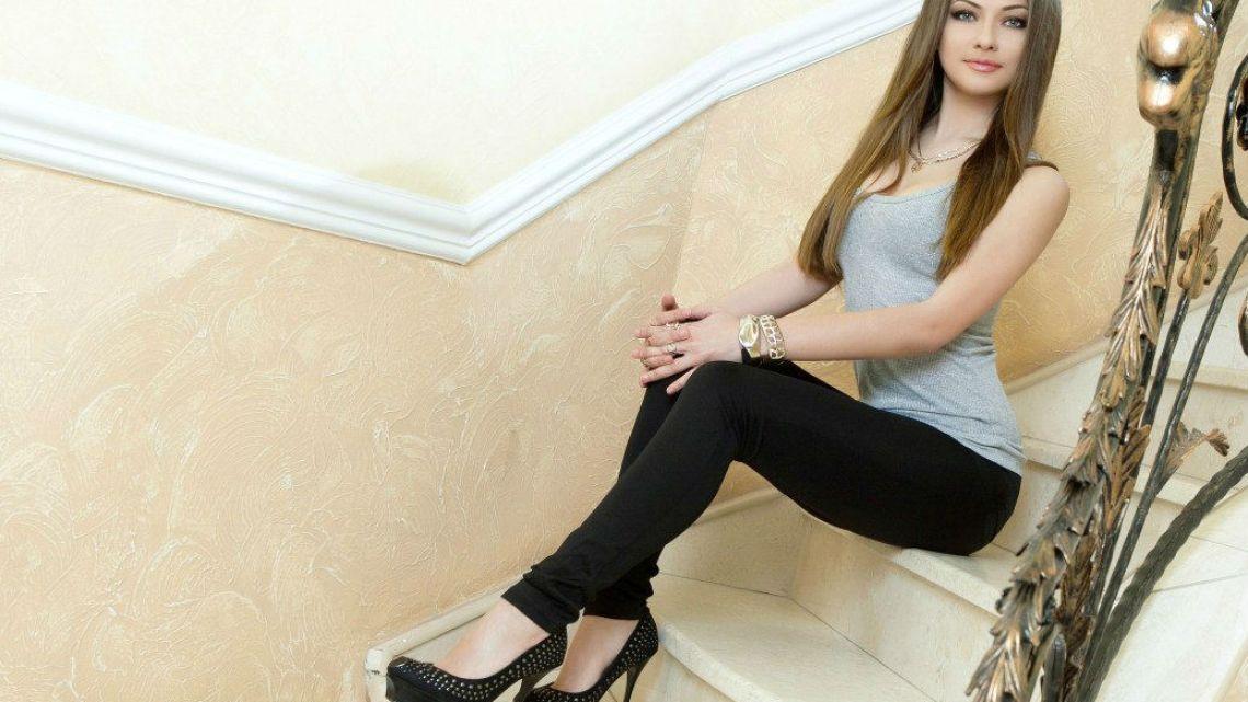 Девушка  на ступеньках в джинсах