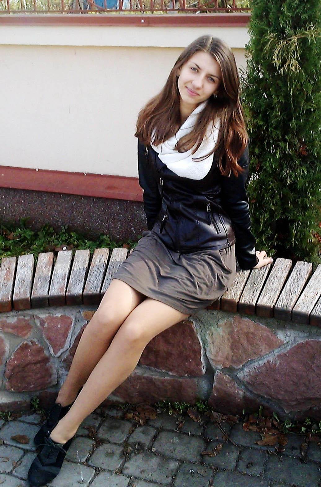 Красивая шатенка на скамейке в платье