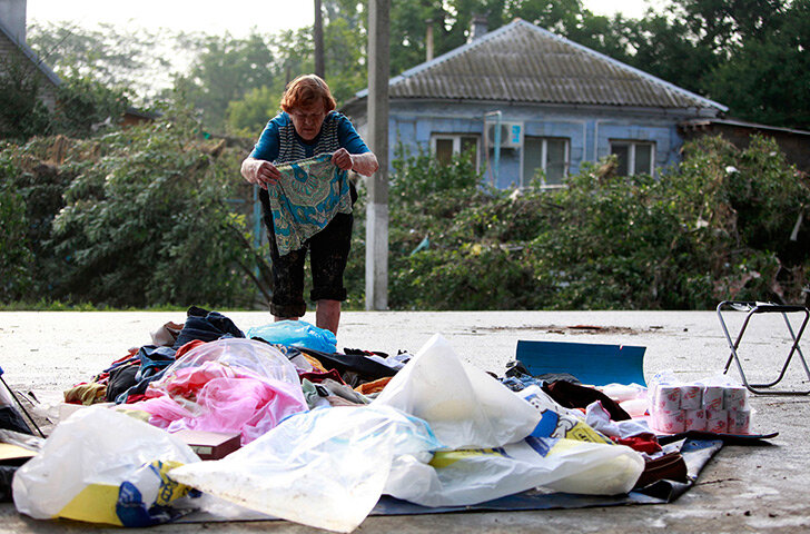 A local resident lays out her belongings on the ground in Krymsk