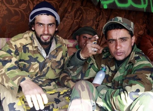 Rebel fighters gesture while smoking hashish in a tent near a tank along the road between Ajdabiyah and Brega