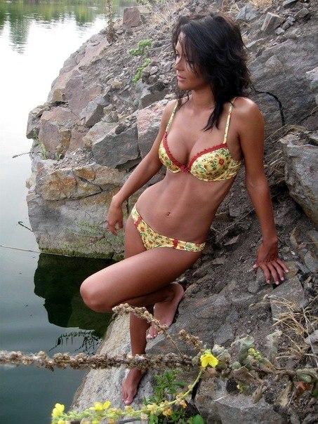 Брюнетка на камнях в купальнике