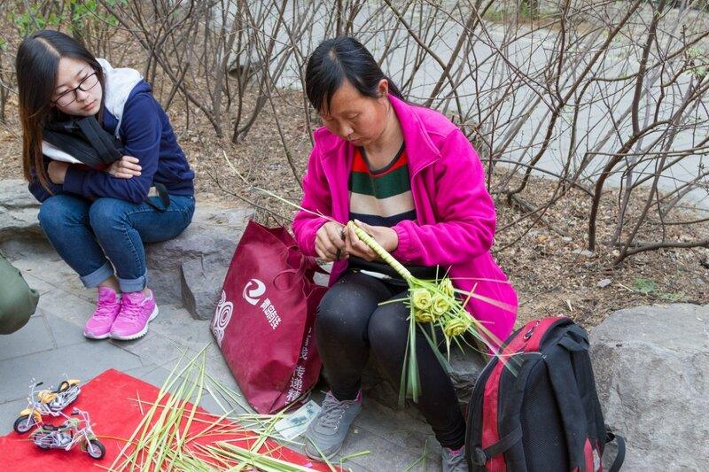 Женщина плетет из травы букет цветов, парк Сяншань, Пекин