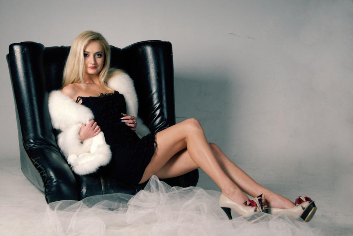 Голубоглазая блондинка в студии на каблуках