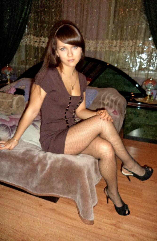 Девушка  в  сетчатых колготках на скамейке