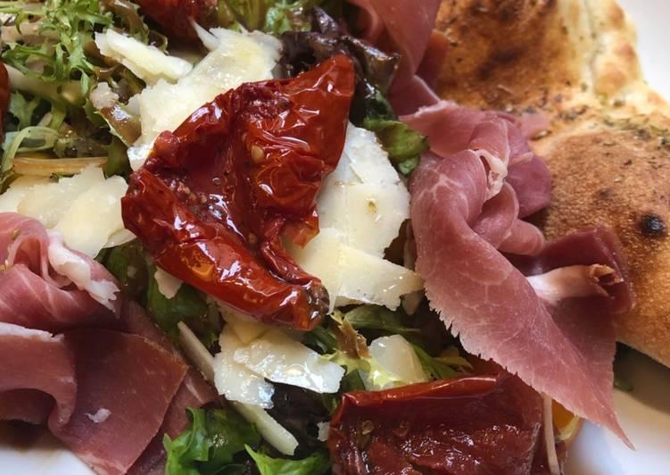 Chausson chèvre sur lit de salade tomates séchées, jambon de parme, parmesan