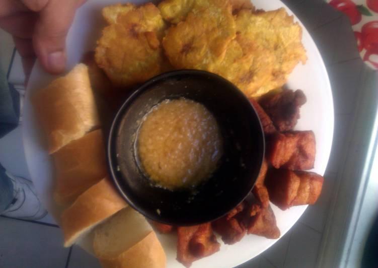 Carnitas fritas con tostones garlic sauce and long bread...