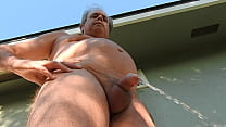 Nude mature man draining his penis, outside, in his backyard.