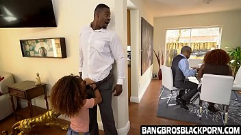 Black teen sucks her step dad while her mother is talking with her grand-father in the kitchen.