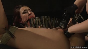 Young lesbian in rope cocoon bondage standing gagged and getting whipped by mistress then getting pussy fisted with clamped body
