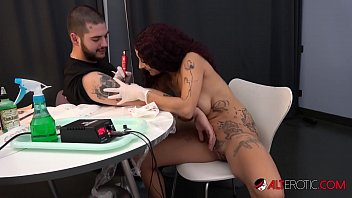 Sexy brunette with big tits sucks and fucks while giving a tattoo