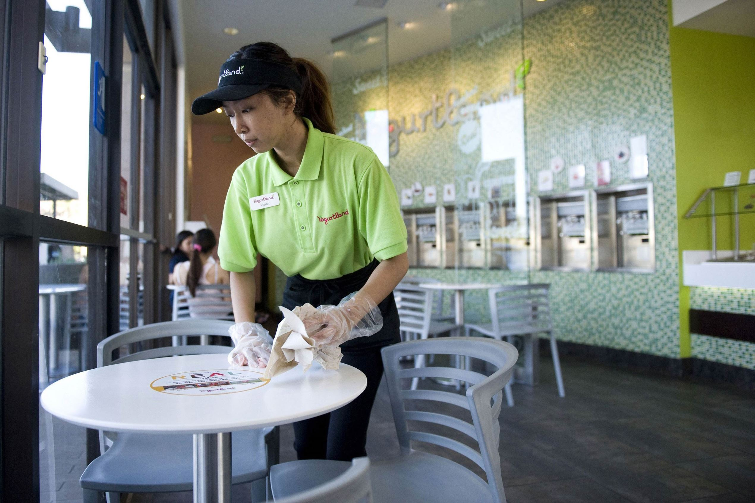 Vivian Pham, 20, wipes down tables during her summer job as an associate at Yogurtland in Huntington Beach, Calif. Pham is a second-year student at Golden West College.