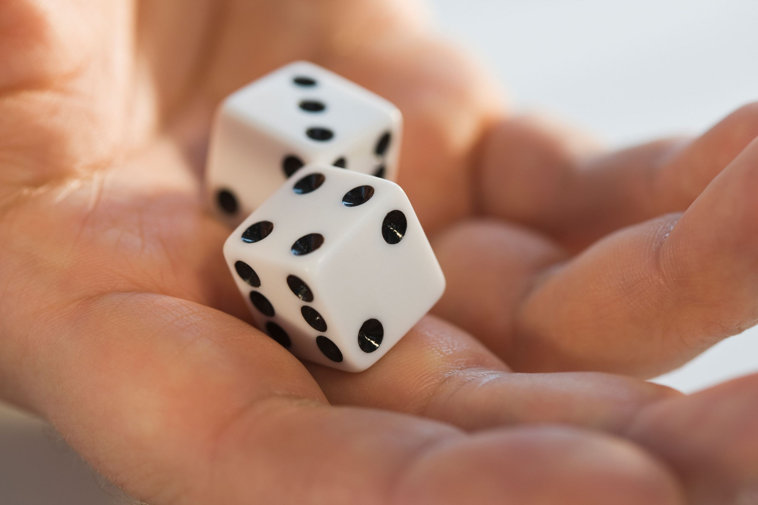 Close up of dice in man's hand.