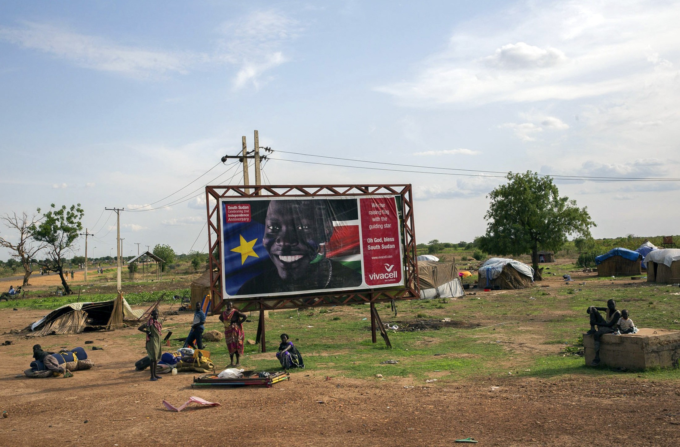 South Sudanese citizens gather in 2014 in front of a sign celebrating the anniversary of the country's independence, as they prepared to flee from renewed attacks in Bentiu.
