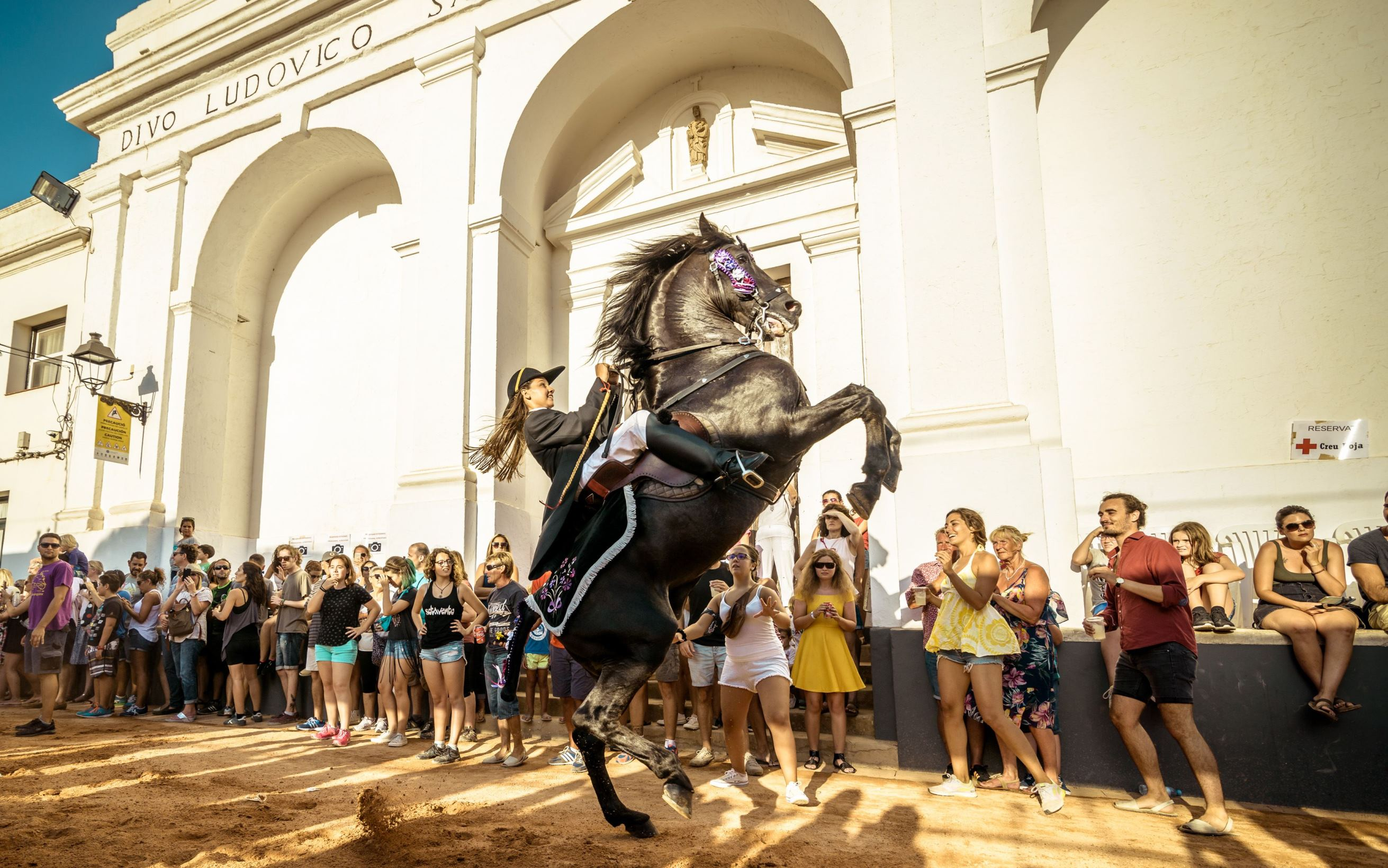 Слайд 10 из 67: St Lluis Patron Saint Festival, Spain - 27 Aug 2016 A 'caixer' (horse rider) rears up on her horse in front of the spectators as he rides through the streets at the beginning of the traditional patron saint fiesta in Sant Lluis