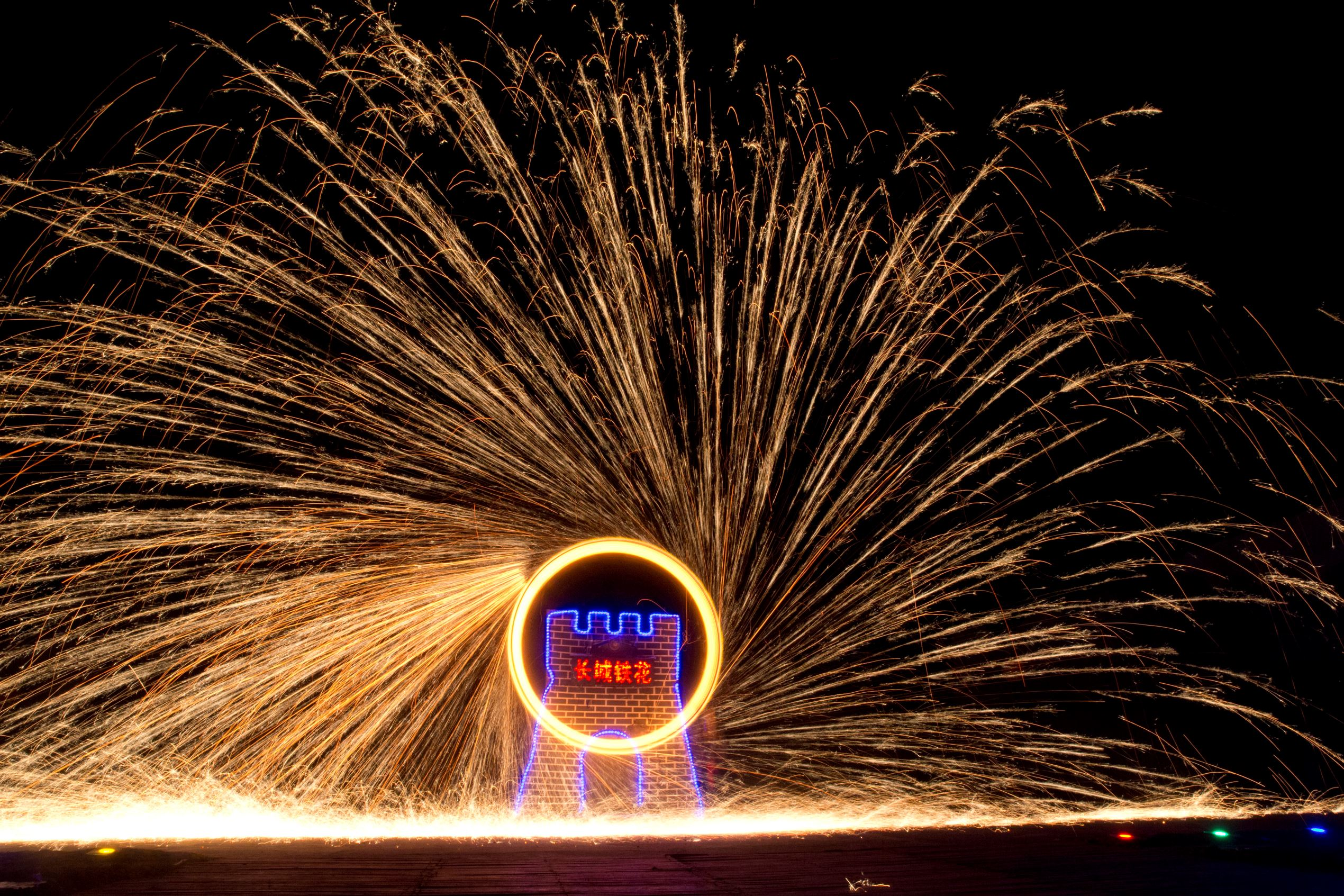 Performers turn a wheel spinning molten iron to create sparks at the Great Wall Iron Sparks show in Yanqing county on the outskirts of Beijing, China on Jan. 28.  Ng Han Guan/AP Images