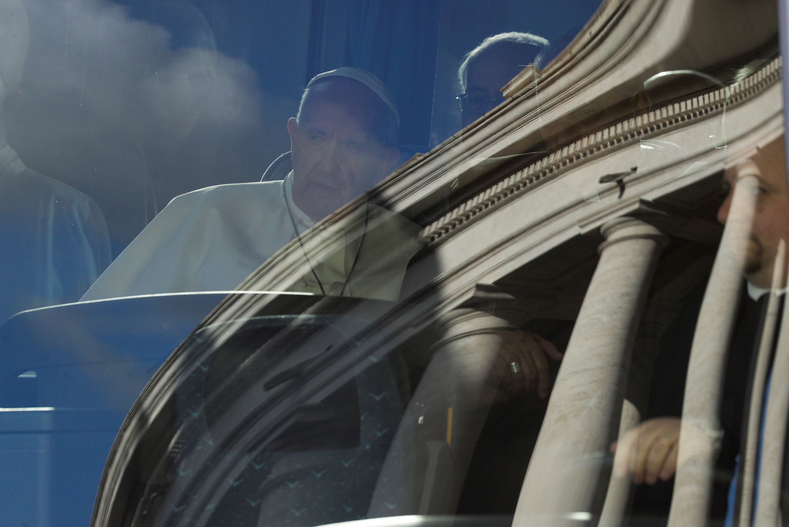 Pope Francis sits on a bus as the Bernini colonnade is reflected on the windscreen, at the Vatican, Sunday March 5, 2017.