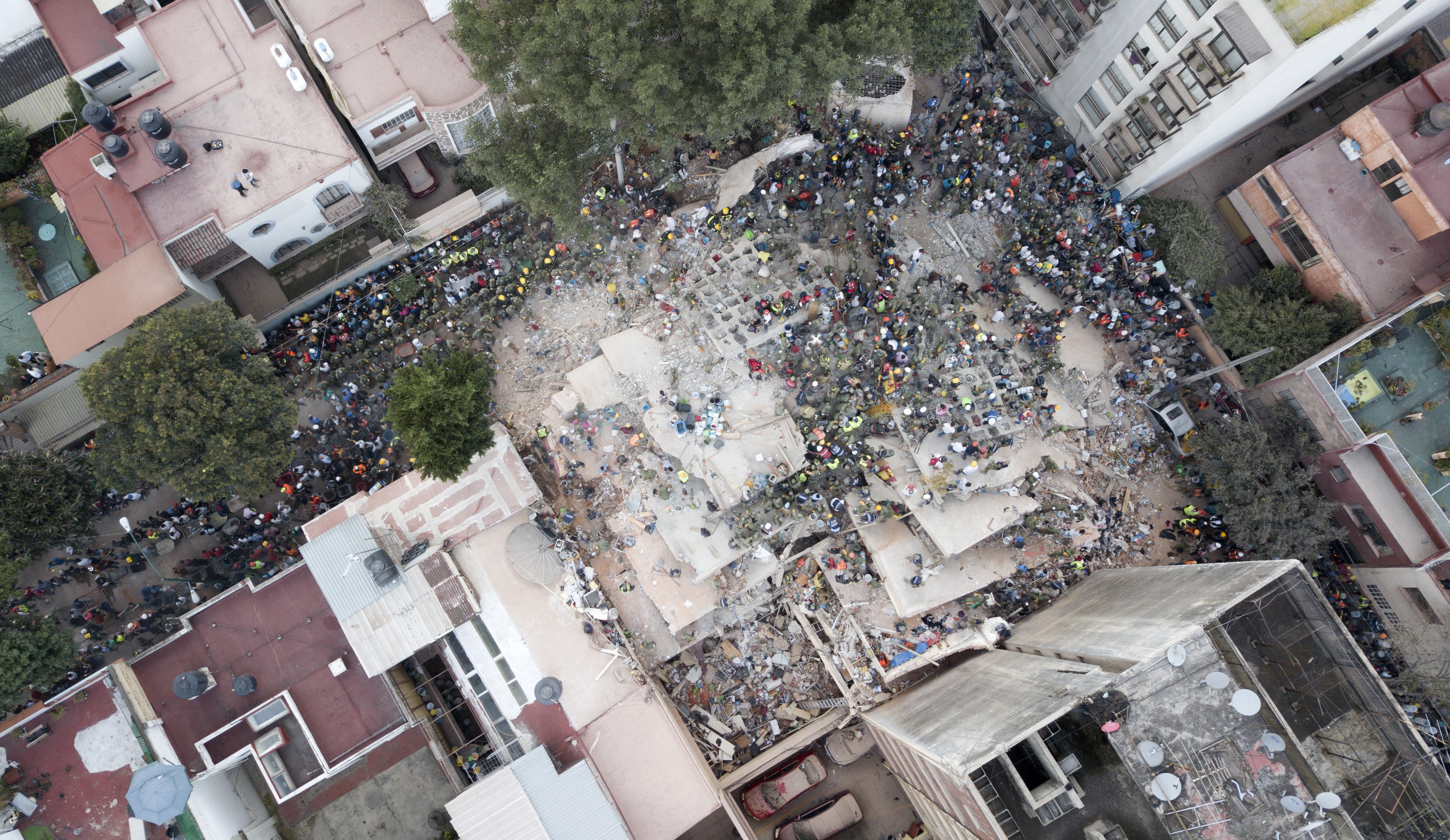 Slide 1 of 42: Rescue workers and volunteers search for survivors on a collapsed building the Del Valle neighborhood in Mexico City, Tuesday Sept. 19, 2017. A magnitude 7.1 earthquake has stunned central Mexico, killing more than 100 people as buildings collapsed in plumes of dust. (AP Photo/Miguel Tovar)
