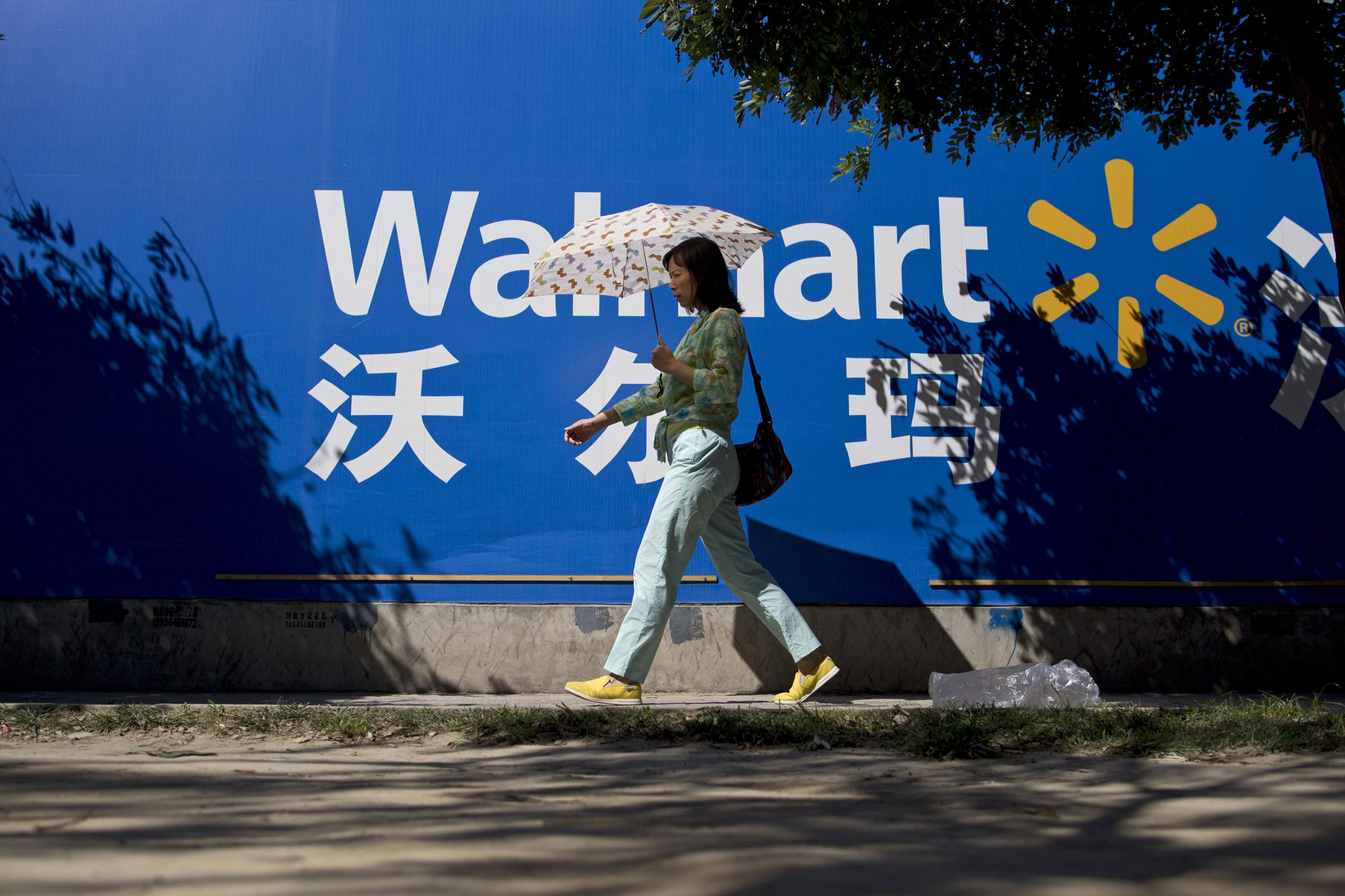 A woman holding an umbrella walks past signage for Wal-Mart Stores Inc. in Beijing, China, on Monday, Sept. 8, 2014. China is scheduled to release figures on consumer and producer prices on Sept. 11. Photographer: Brent Lewin/Bloomberg