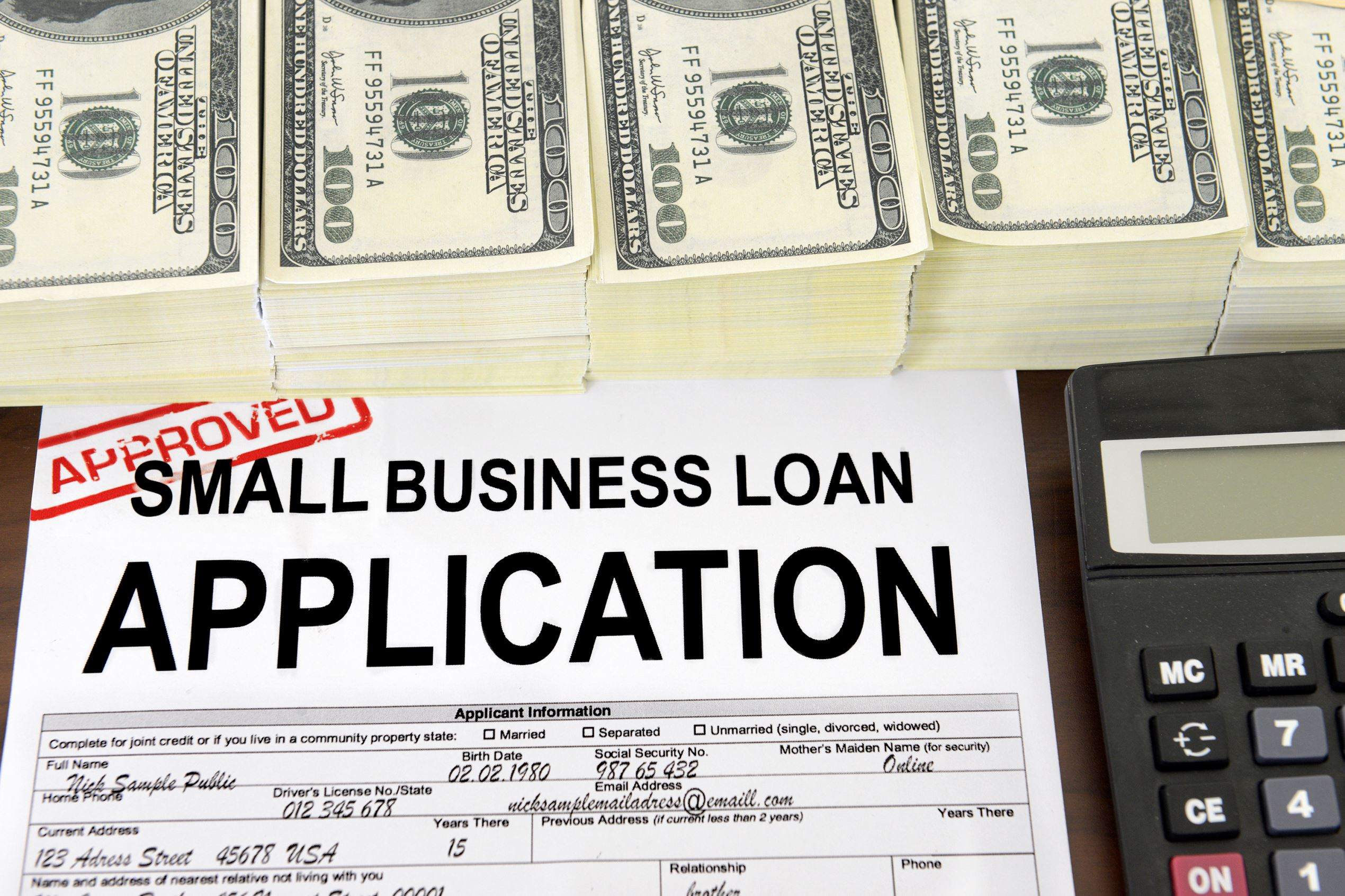 Application for a small business loan and US dollar bills. Mangostock/Getty Images