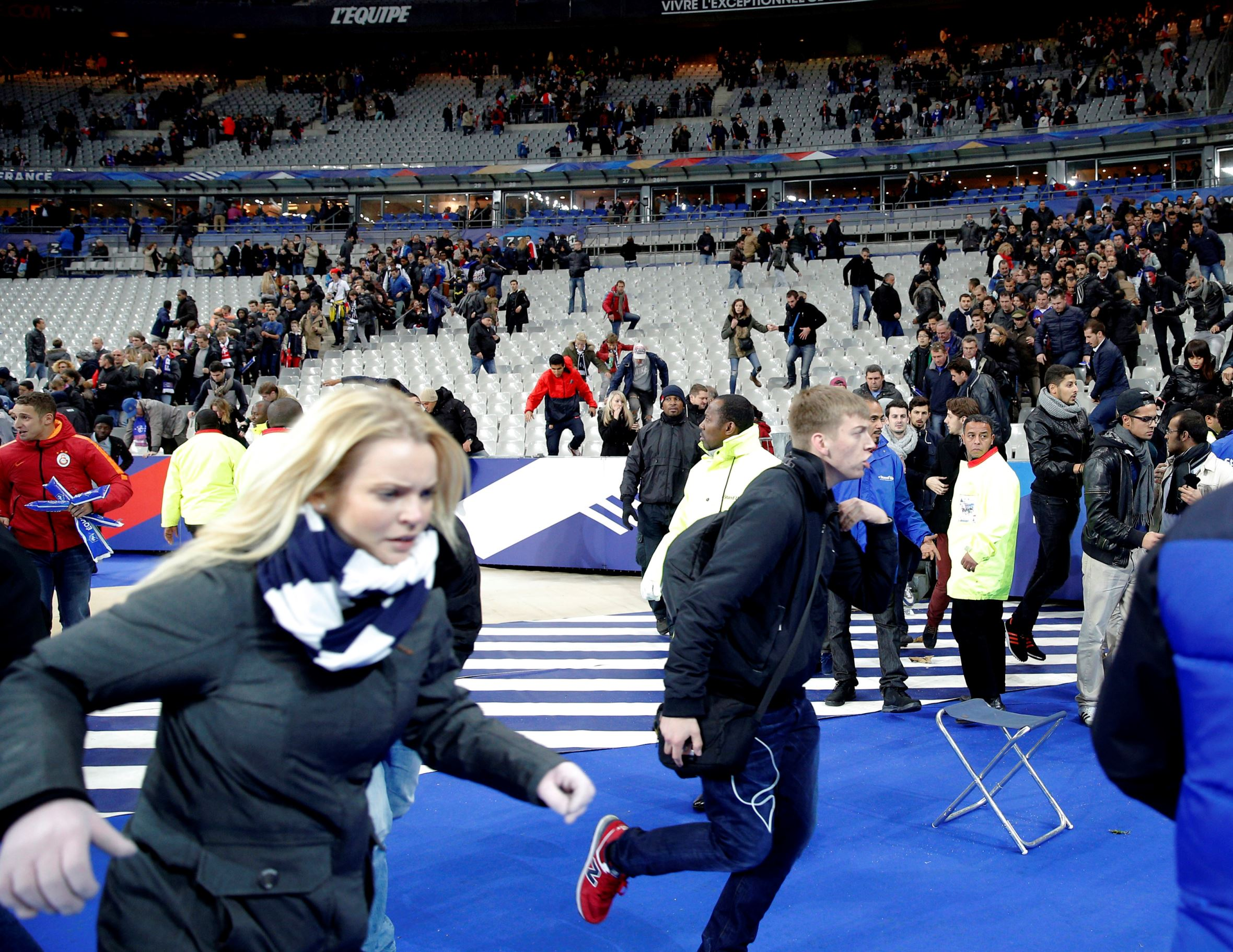 Spectators run onto the pitch of the Stade de France stadium after the international friendly soccer match between France and Germany in Saint Denis, outside Paris, on Nov. 13, 2015, after explosions were heard nearby.