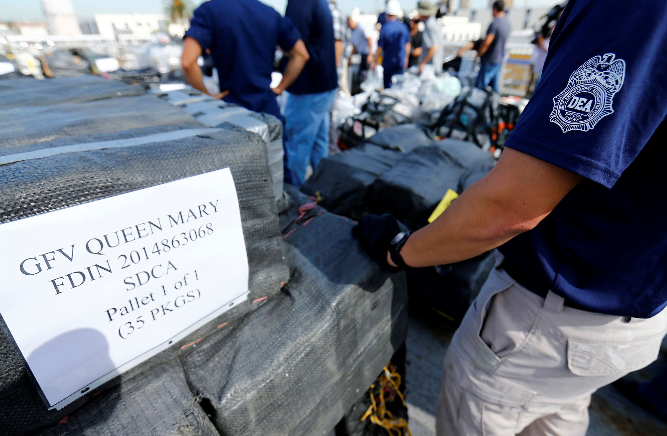 Drug Enforcement Agency (DEA) agents take inventory of seized cocaine packages, at Naval Base San Diego, October 6, 2014. Some 28,000 pounds (12.7 ton) of cocaine were seized by U.S forces in 18 separate interdictions.