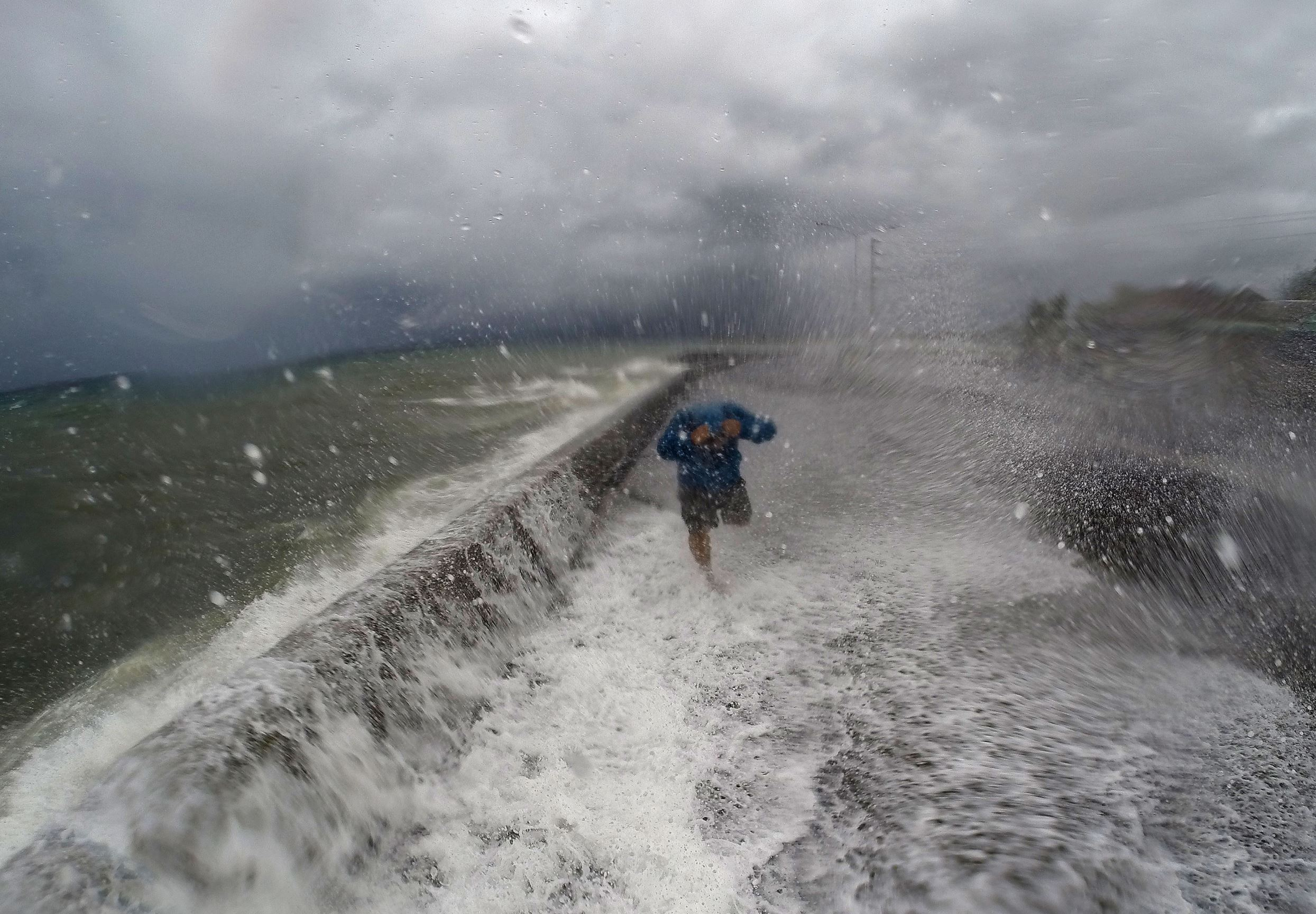 A resident walks past big waves spilling over a wall onto a coastal road in the city of Legaspi in Albay province, south of Manila on December 14, 2015, as typhoon Melor approaches the city. More than 700,000 people fled the central Philippines amid threats of giant waves, floods and landslides as powerful Typhoon Melor approached the archipelago nation, officials said December 14.