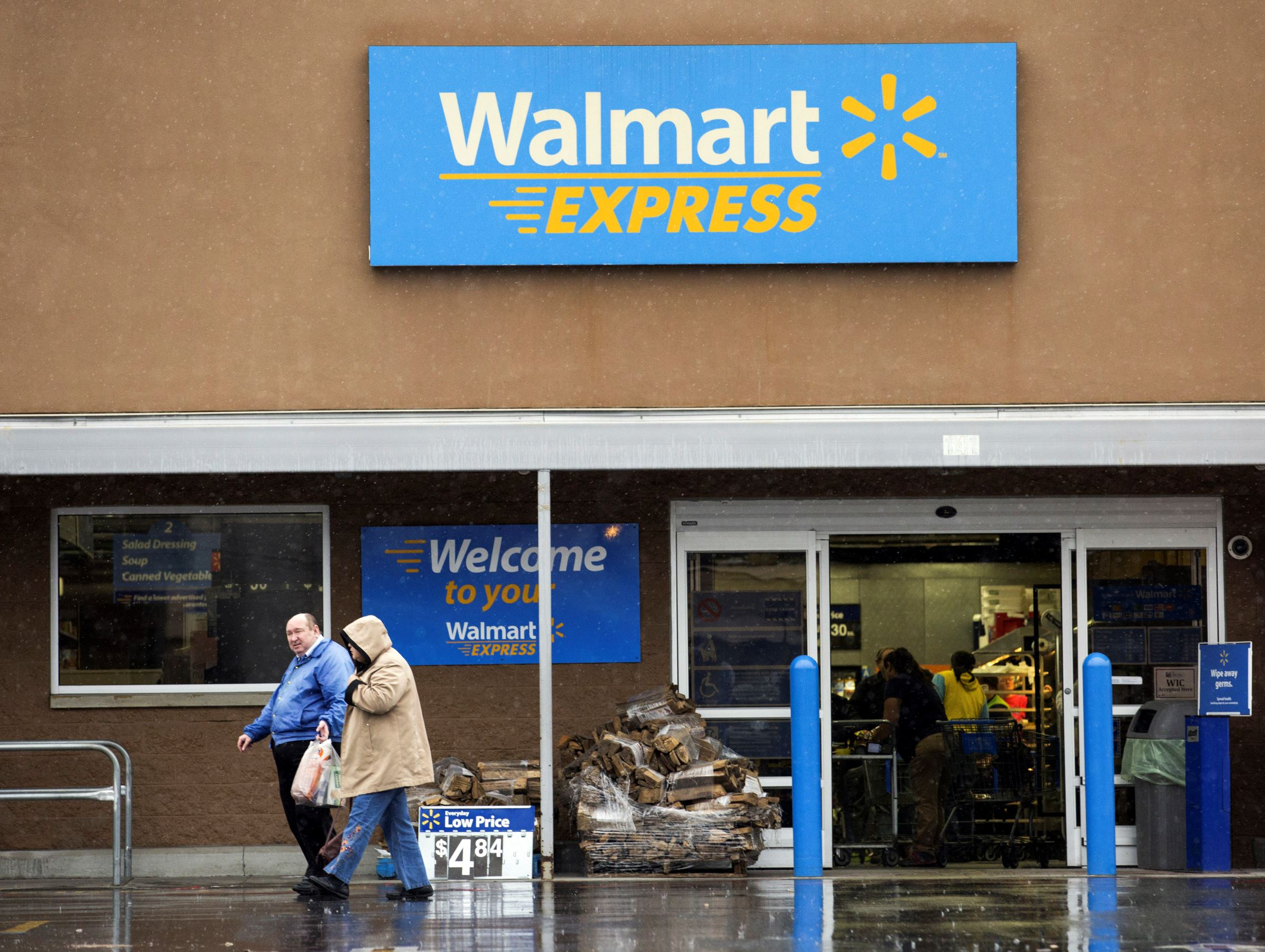 Customers exit a Wal-Mart Express store in Richfield, North Carolina, U.S.. Wal-Mart Stores Inc. plans to close 269 store, including its experimental small-format Express outlets, in a much to streamline the chain that will eliminate 16,000 jobs.
