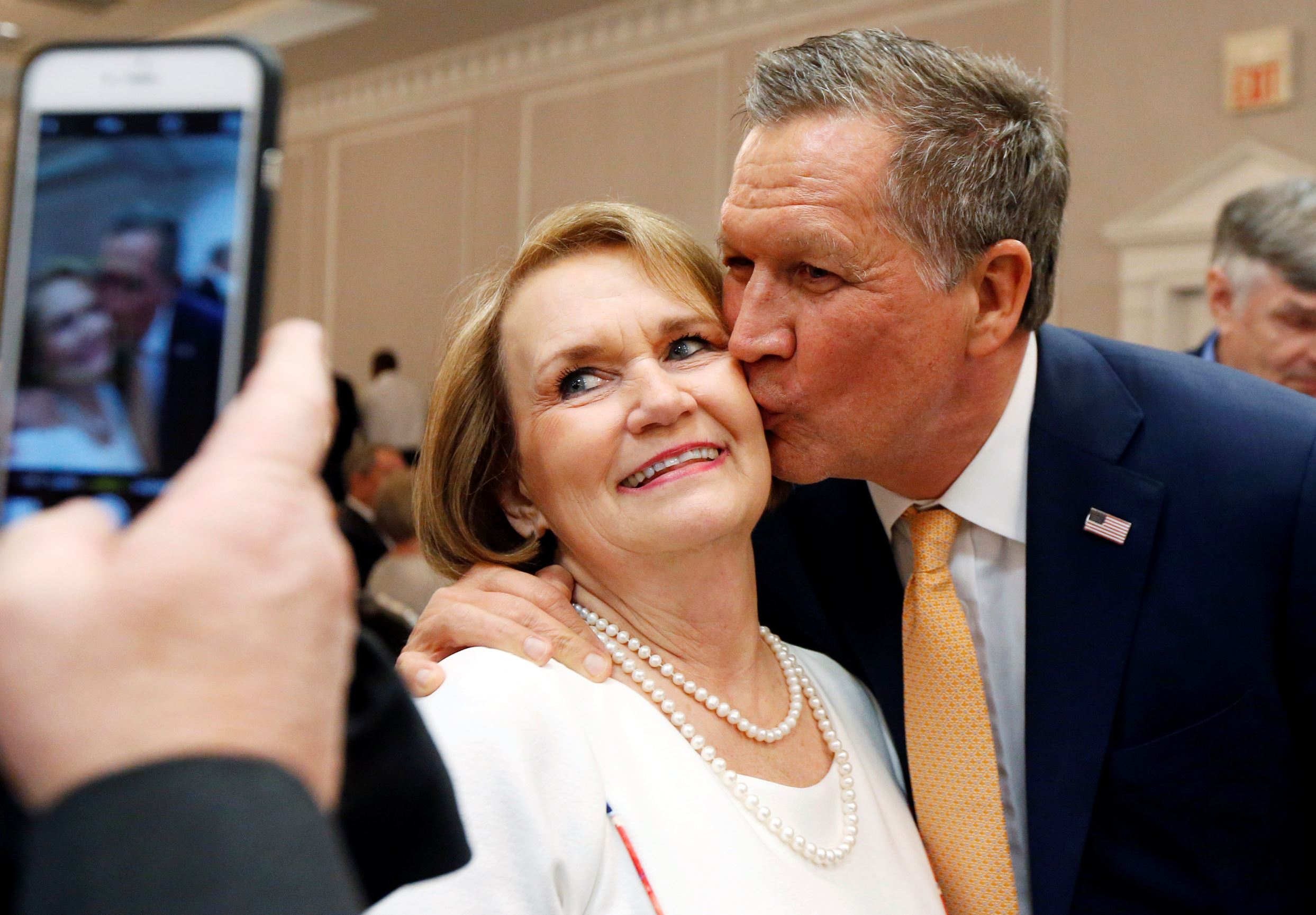 Republican presidential candidate Ohio Gov. John Kasich kisses the cheek of Kay Ward of Louisville, Miss., as she has her photo taken prior to addressing a Central Mississippi Republican Party fund raising dinner in Jackson, Miss., Tuesday, March 1, 2016.