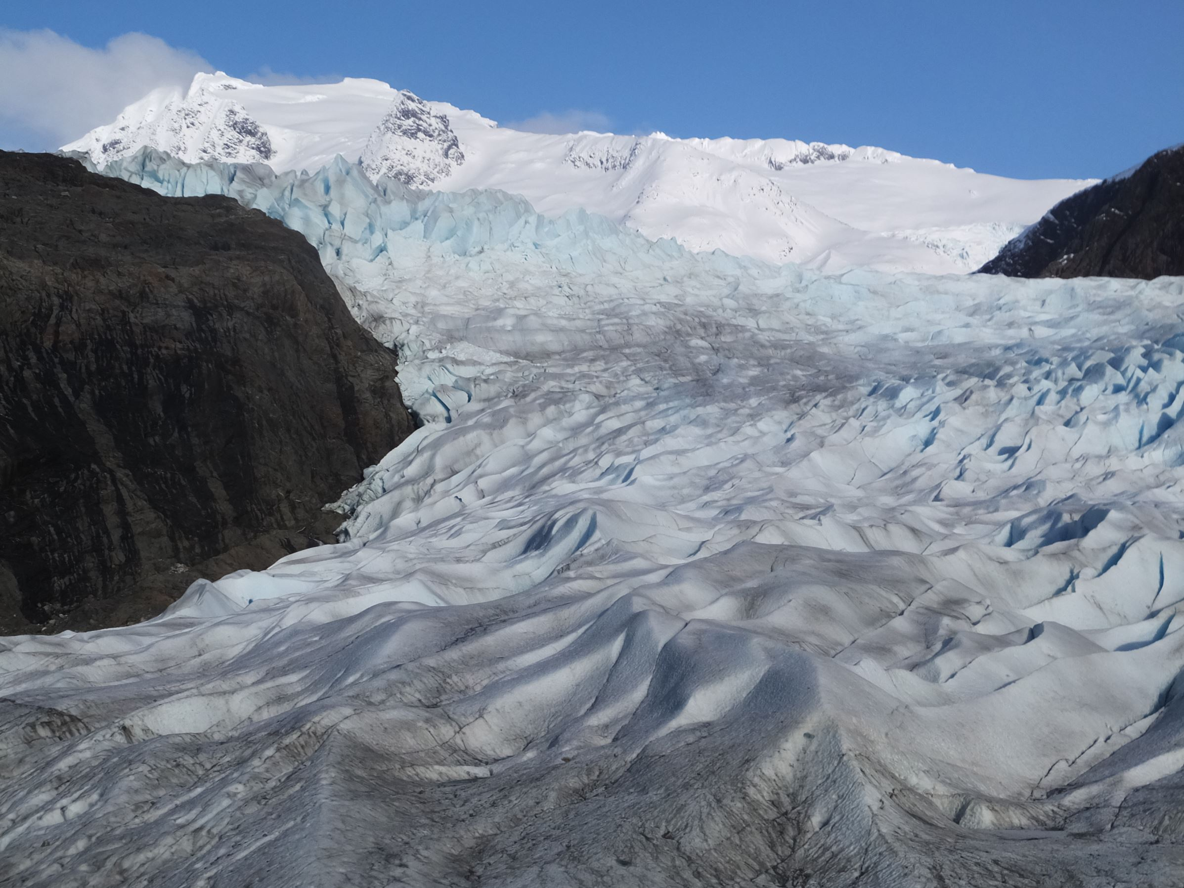 File - In this Feb. 15, 2016 file photo, snow-covered mountains are seen behind the Mendenhall Glacier in Juneau, Alaska. The massive Alaska ice field that feeds Juneau's Mendenhall Glacier, a tourist attraction viewed by hundreds of thousands each year, could be gone by 2200 if climate warming trends continue, according to a new University of Alaska Fairbanks study.