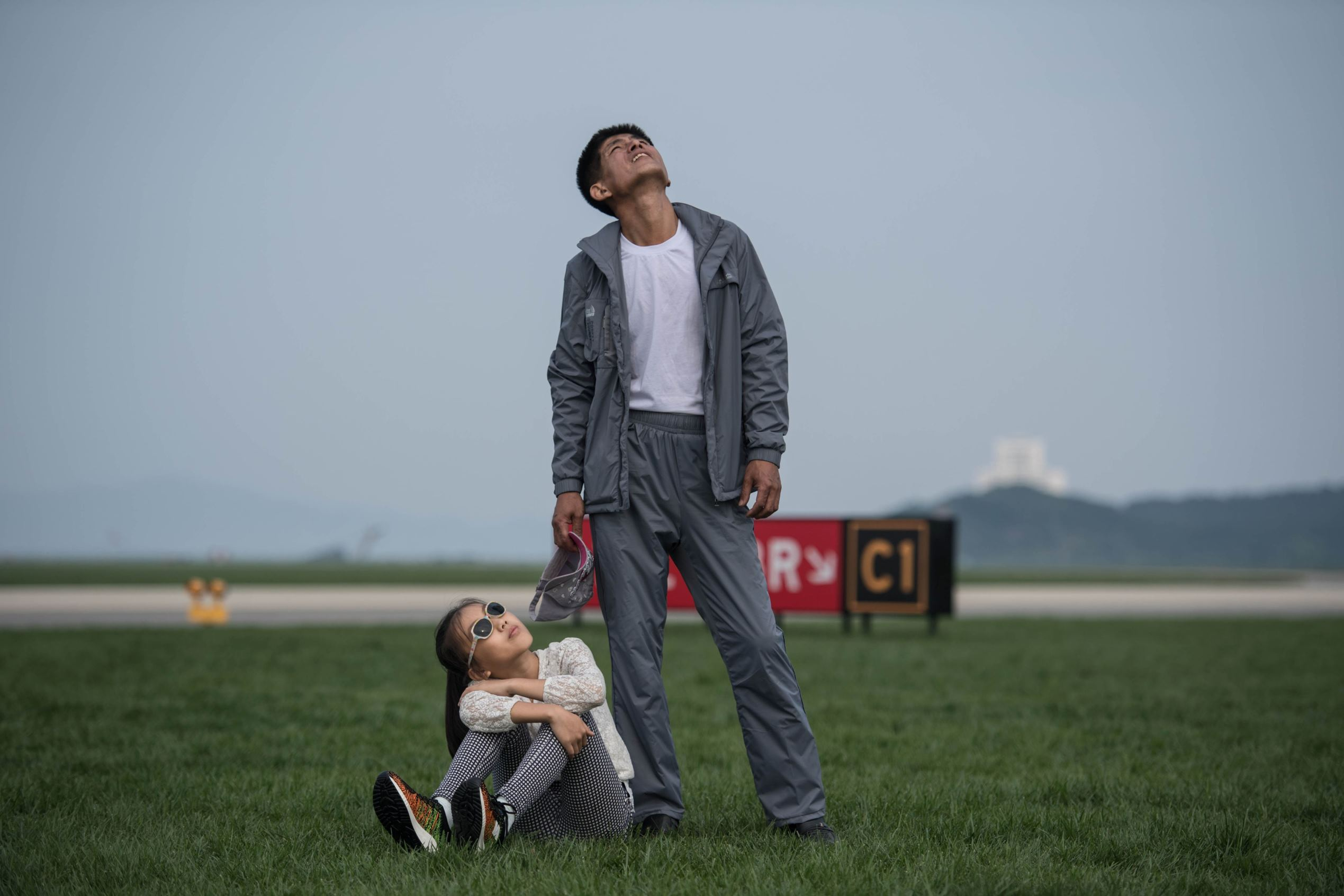 A man and child watch a aerial display during the Wonsan Friendship Air Festival in Wonsan on Sept. 25, 2016.