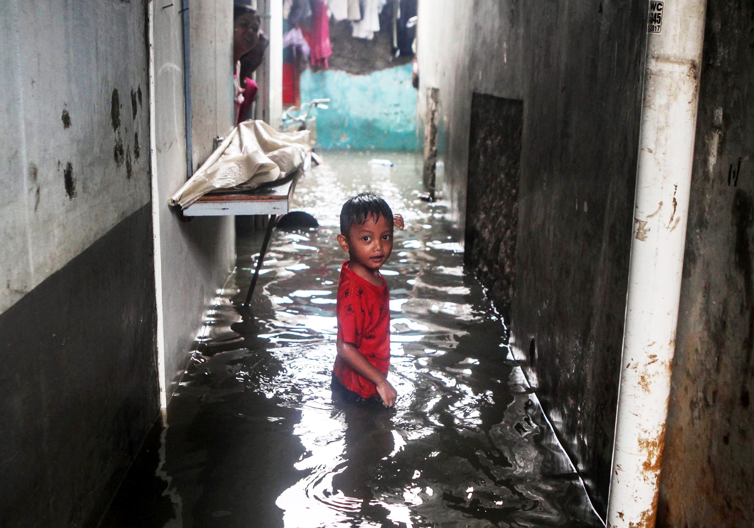Слайд 24 из 86: JAKARTA, INDONESIA - FEBRUARY 26: A young boy looks on as residential areas remain flooded after heavy rain overnight in the Indonesia Capital of Jakarta, on February 26, 2016. Seasonal rains and high tides in recent days have caused widespread flooding