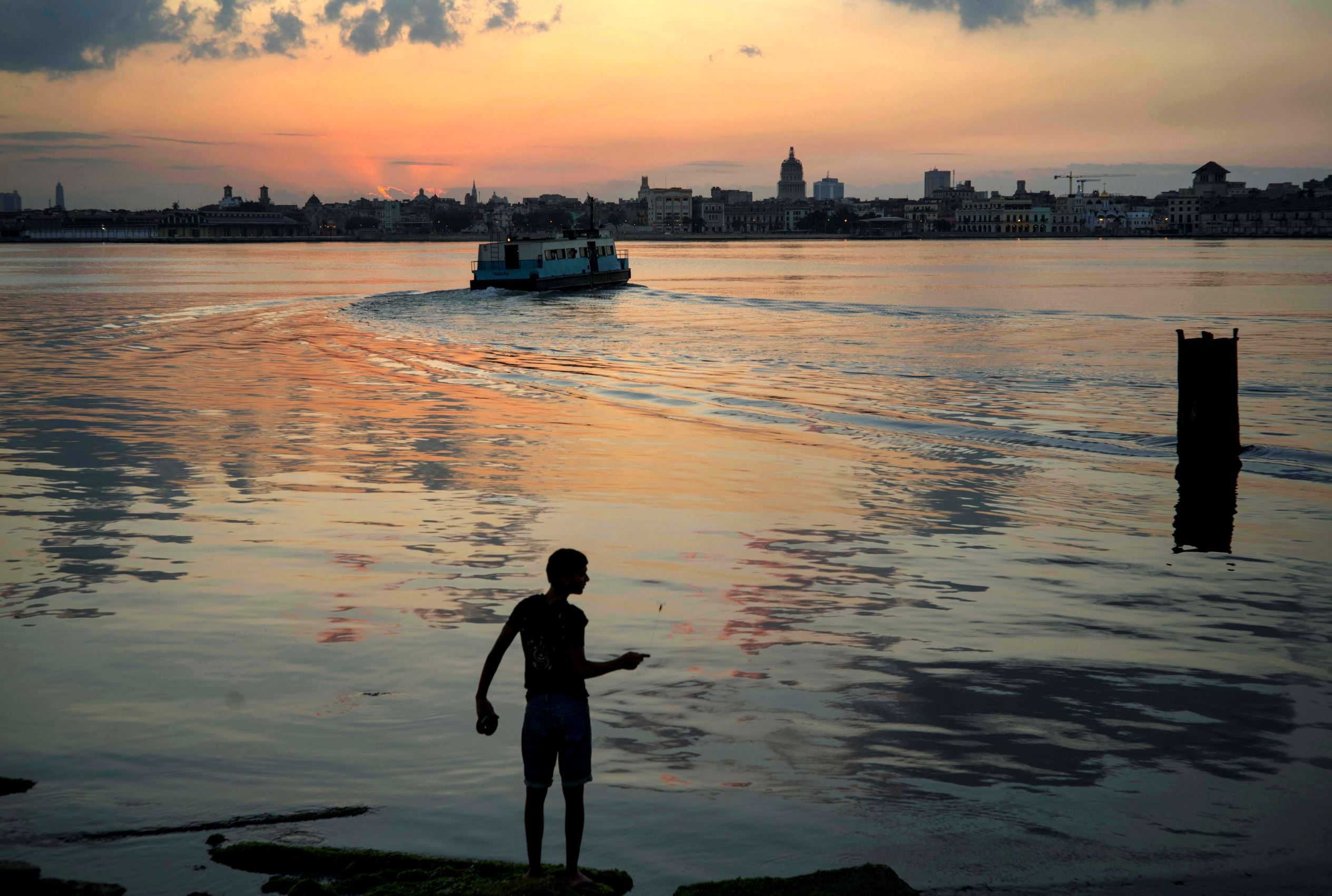 """Слайд 30 из 86: A youth fishes by hand using fishing line on the shores of Regla, as commuters cross the bay by ferry to Havana, Cuba, Monday, March 14, 2016. People who fish here tend to catch small sardines and a fish known as """"bonito."""" U.S. President Barack Obama wil"""