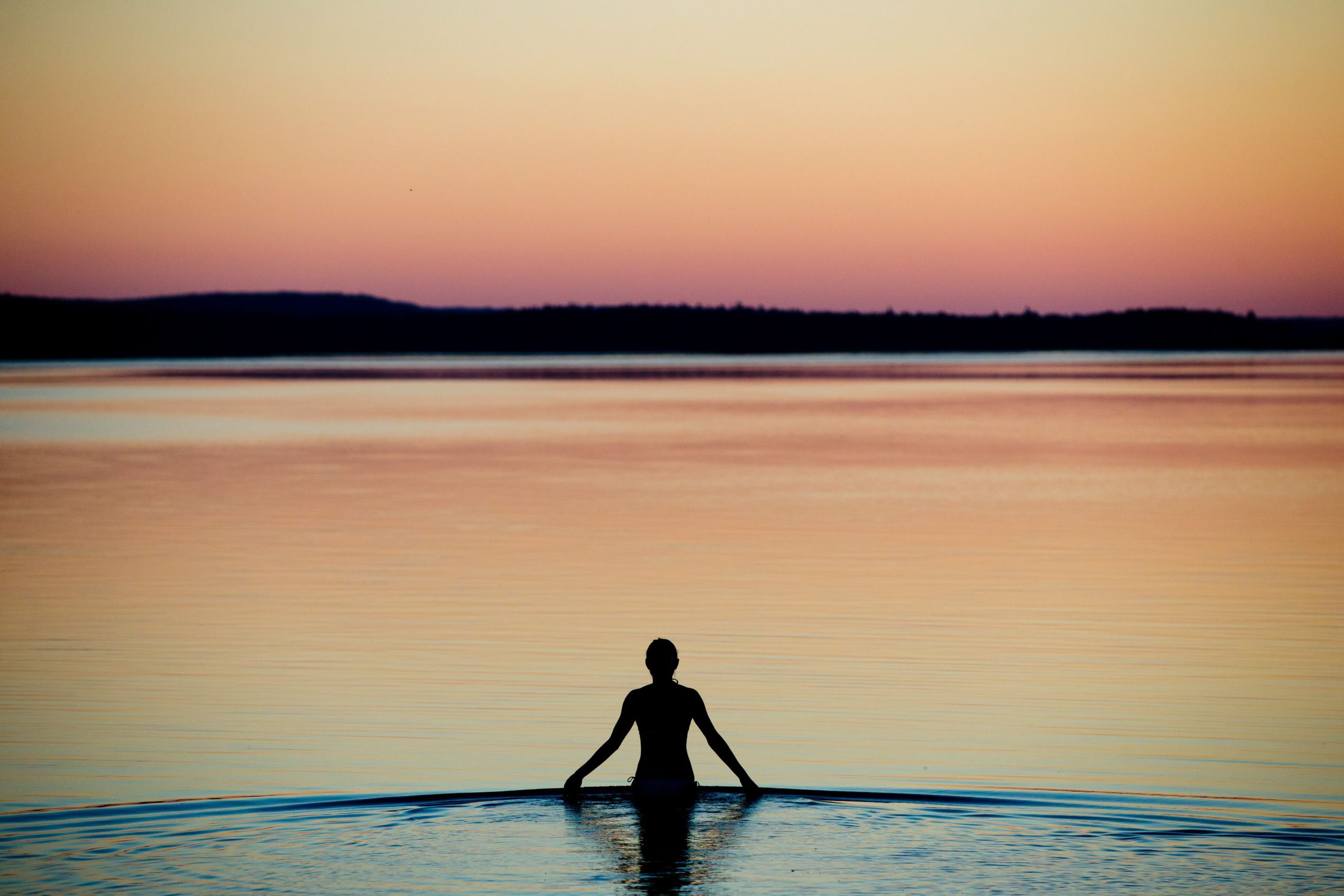 Слайд 57 из 86: epaselect epa05386975 A photo made available 24 June 2016 of a young woman wading in the shallow waters of the Brombach Lake near Pleinfeld, Bavaria state, Germany, as the sun sets here on 23 June 2016 evening. EPA/DANIEL