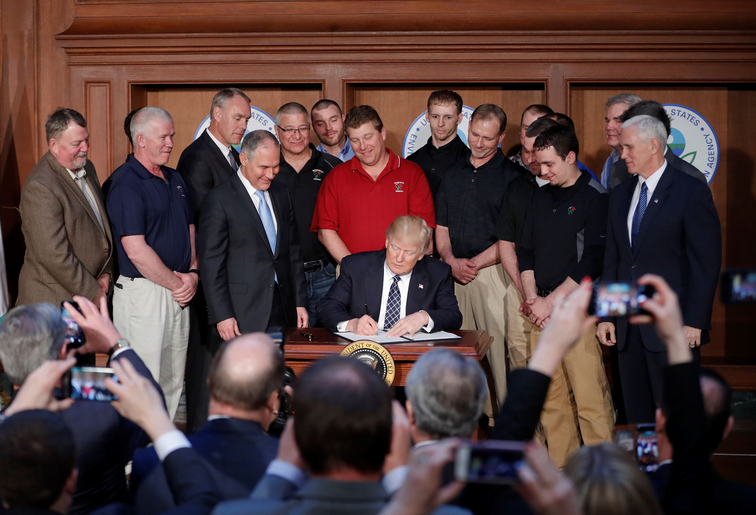 President Donald Trump, accompanied by Environmental Protection Agency (EPA) Administrator Scott Pruitt, third from left, and Vice President Mike Pence, right, signs an Energy Independence Executive Order, Tuesday, March 28, 2017, at EPA headquarters in Washington.