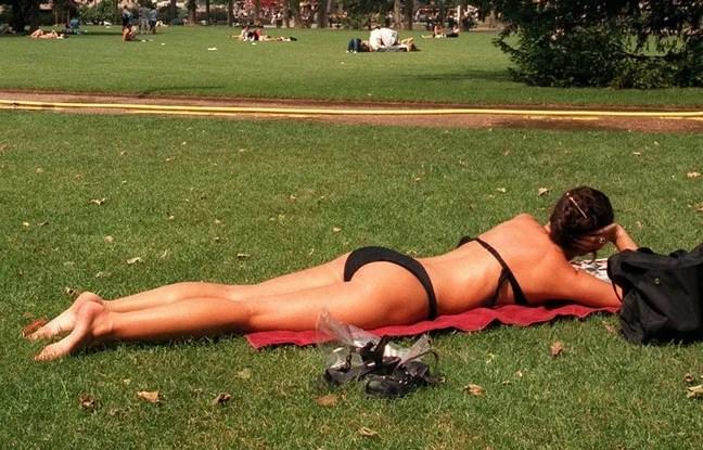 Une femme allongée dans l'herbe bronze en maillot de bain, à Paris. Image d'illustration.