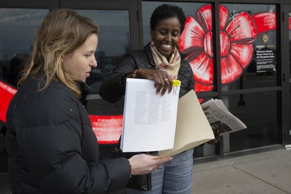 A woman gives a stack of papers to another woman in front of a warehouse.
