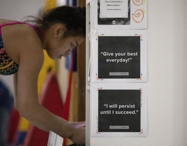 Print outs with motivational quotes are taped to a shelf.