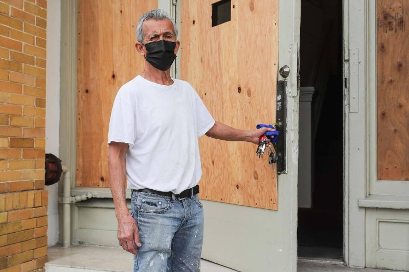 A man with grey hair wearing a black surgical mask opens a boarded up door into a hotel lobby.