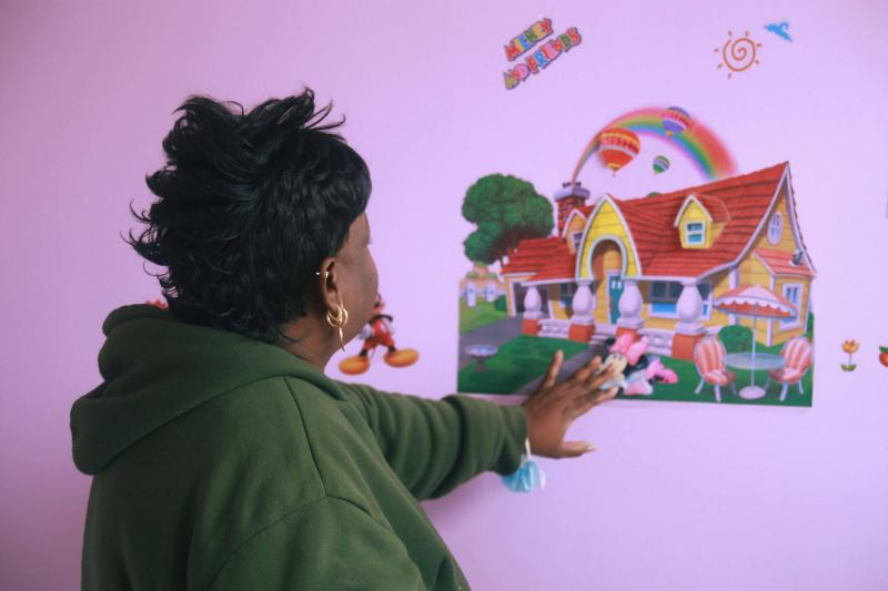 Jackie looking at a rainbow wall decoration of a cottage at one of her daycare centers.