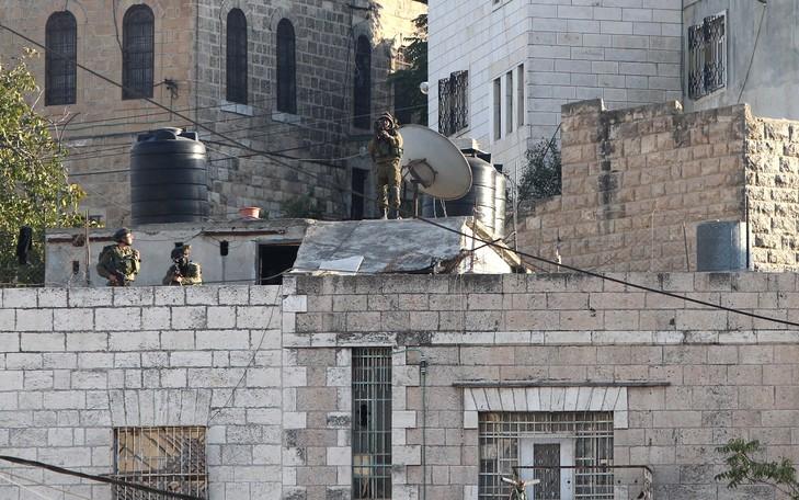 Image d'archives prise le 21 octobre 2015 montrant des membres des forces de sécurité israéliennes sur le toit d'une maison à Hébron pendant des affrontements avec des manifestants palestiniens / AFP/Archives