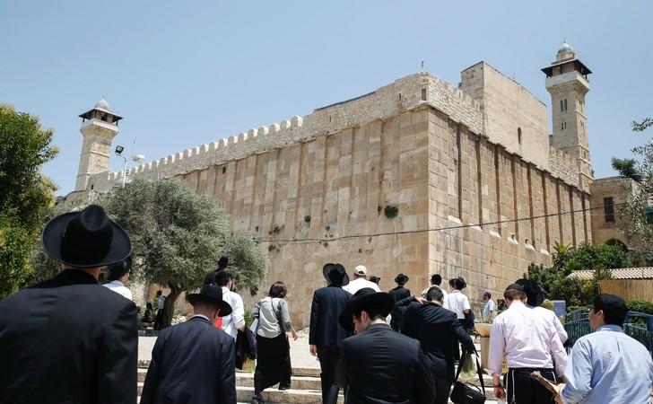 Des religieux juifs et des touristes marchent vers le Tombeau des Patriarches, également appelé Mosquée d'Ibrahim, à Hebron, le 7 juillet / AFP