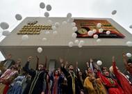 Les étudiants étrangers portant leurs costumes traditionnels jettent des ballons ...