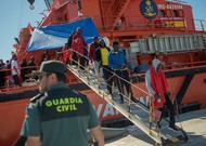 Des migrants secourus en mer débarquent d'un bateau en attente de transfert ...
