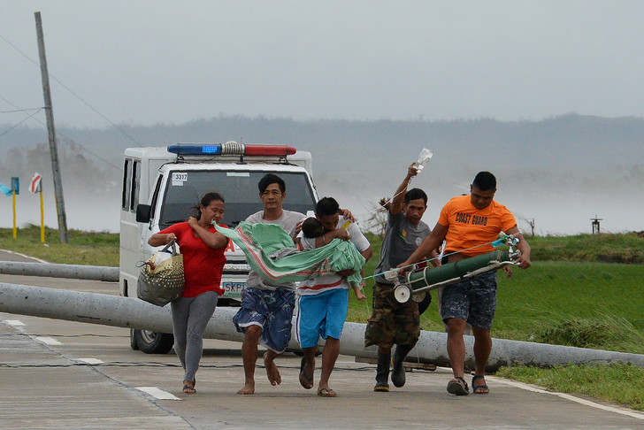 A father carries his sick child to another vehicle while the ambulance carrying him is blocked on a highway by electric poles cut down by Typhoon Mangkhut winds in the Baggao city in the Philippines, September 15, 2018 / AFP
