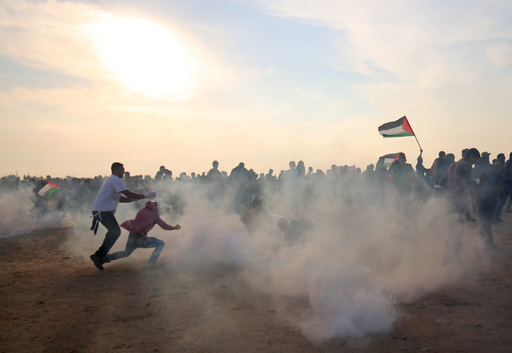 Palestinians flee to escape tear gas during clashes with the Israeli army in Khan Younis, in the southern Gaza Strip, on November 9, 2018 / AFP
