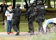 Police remove passersby from the scene of the shooting, on March 15 to Chris ...