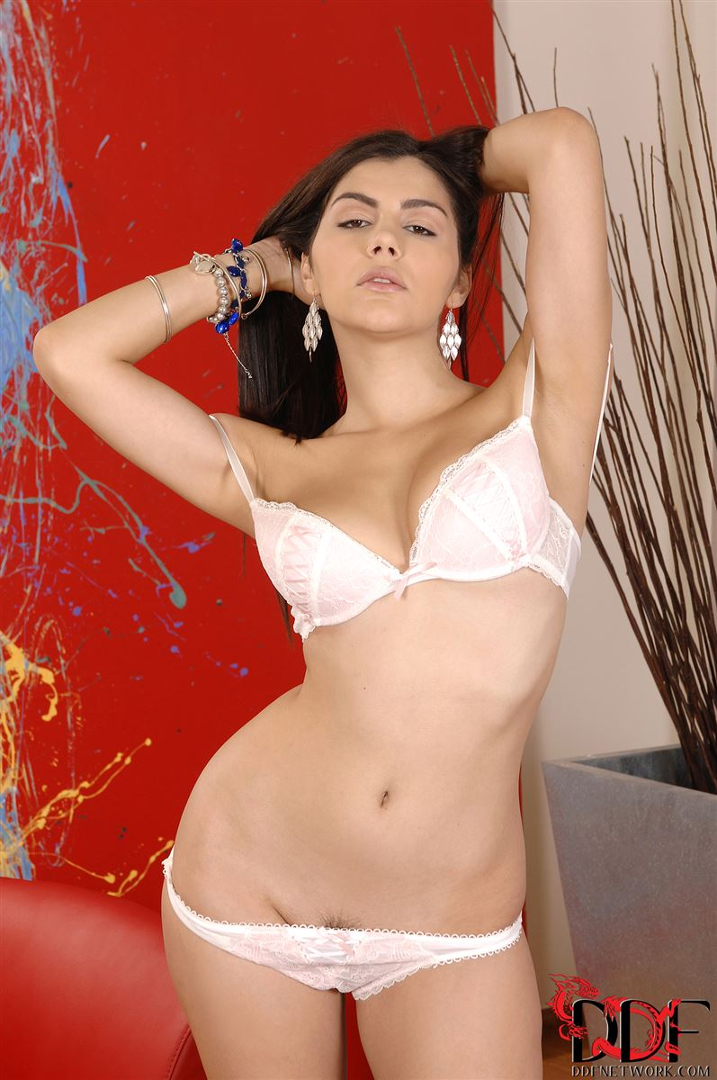 Valentina Nappi poses on a red chair in white lingerie