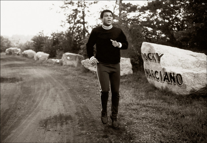 Road work at the Muhammad Ali boxing camp in Deer Lake, Pennsylvania, 1977. Ali had the names of boxing greats painted on the boulders he ran past: Rocky Marciano, Jack Dempsey, Jack Johnson, Joe Louis, and Joe Frazier.